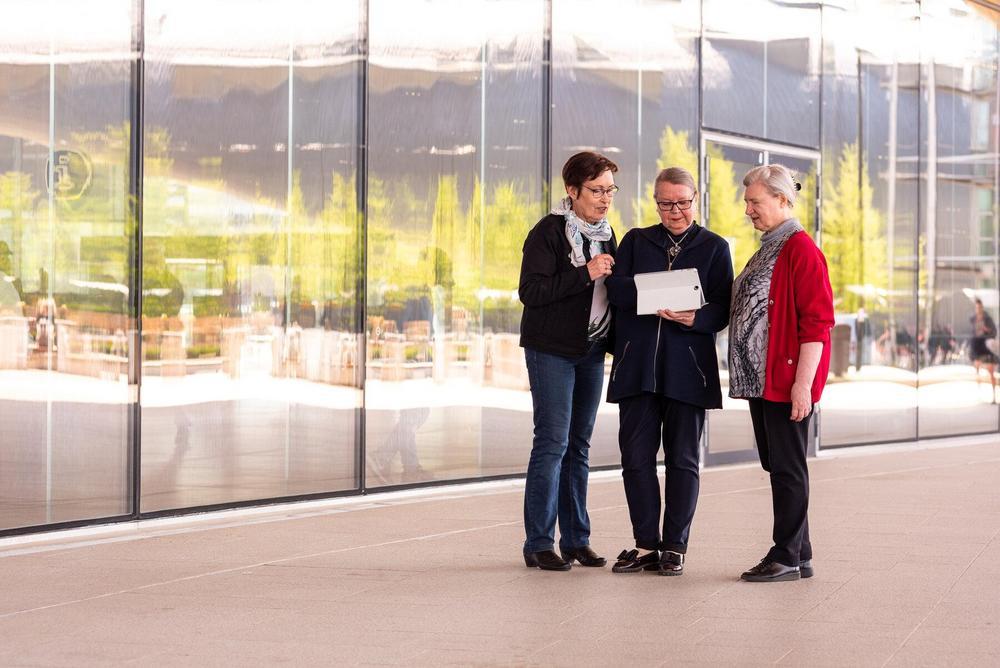 Kuvituskuva: Kolme henkilöä ulkona katselevat tablettia