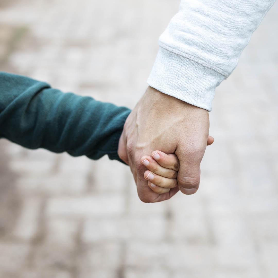 Mies ja lapsi käsi kädessä. Kuva rajautuu niin, että miehen kädestä näkyy vain hieman hihaa ja lapsen kättä pitelevä käsi. Myöskään lapsen kasvoja ei näy.