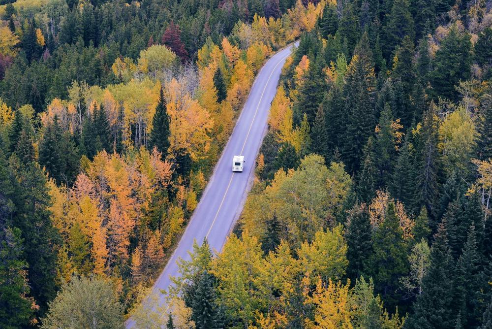 """alt=""""Henkilöauto ajaa tiellä, jota molemmin puolin reunustaa syksyinen metsämaisema."""""""