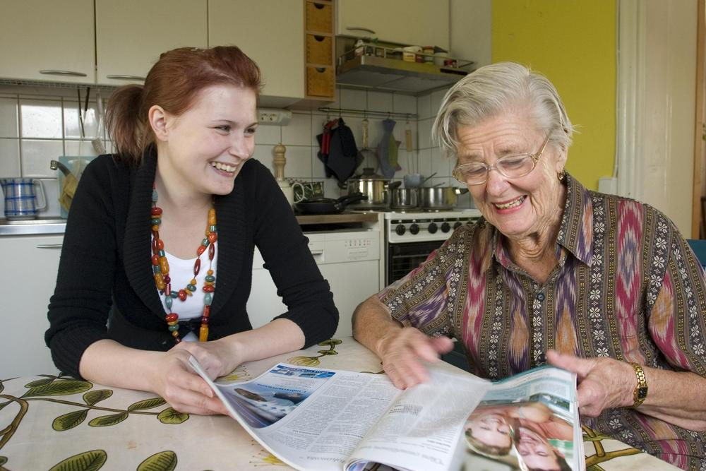 Nuori auttaa vanhusta esim. kotitöissä.