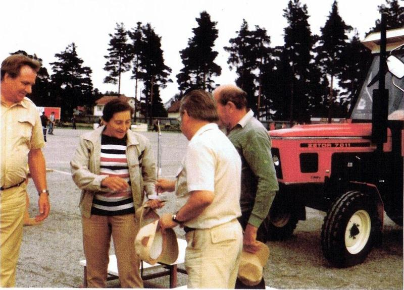 Ankkurien puheenjohtaja Kullervo Rautio luovuttaa seuran viiriä Dana Zatopkovalle Jaakko Filpun ja Emilin seuratessa tilannetta.