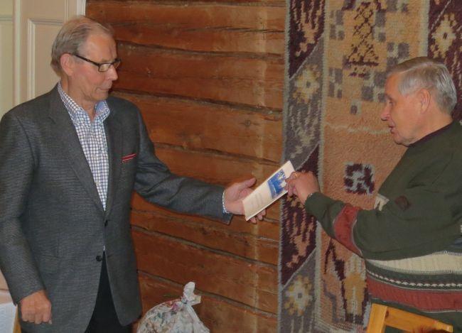 Seuran puheenjohtaja Osmo Kärkkäinen ojensi uudelle puheenjohtajalle Paavo Lintulalle Kisailijoiden 60-vuotishistoriikin.
