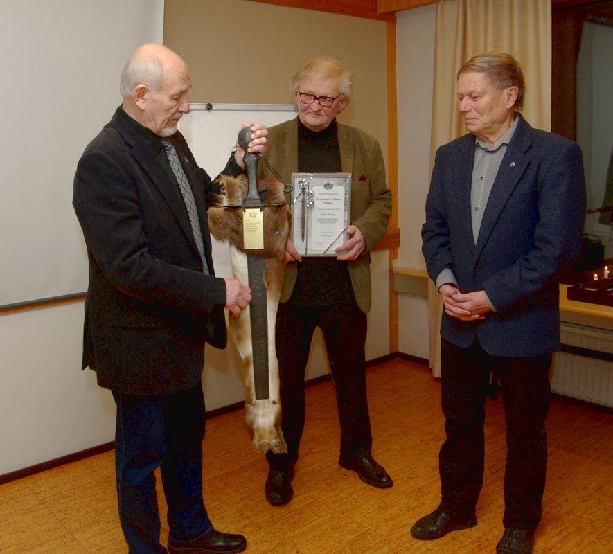 Reijo Rikala (oik.) vastaanottaa miekan edelliseltä haltijalta Kari Rautavalta ja kunniakirjan seuran puheenjohtajalta Esa Palménilta.
