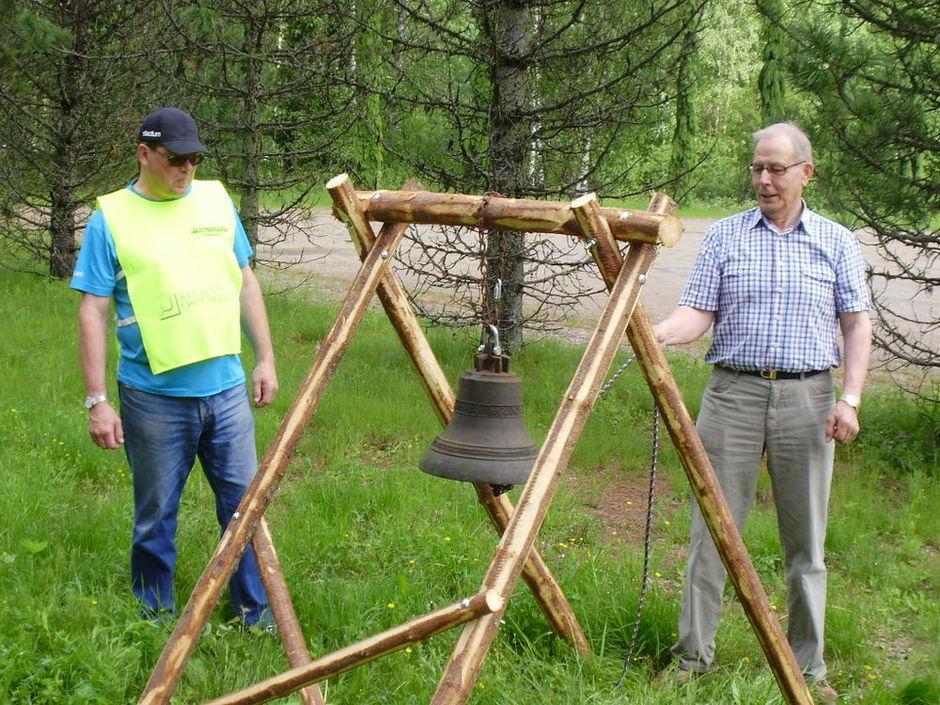 Kisailijoiden puheenjohtaja Paavo Lintula (oik) asensi Kari Vesterisen kanssa lähtömerkkinä käytetyn vellikellon telineeseen.