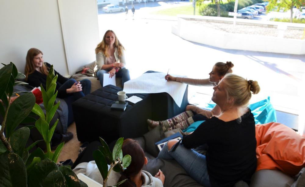 Kouluttajat kokoustamassa kahvilassa.