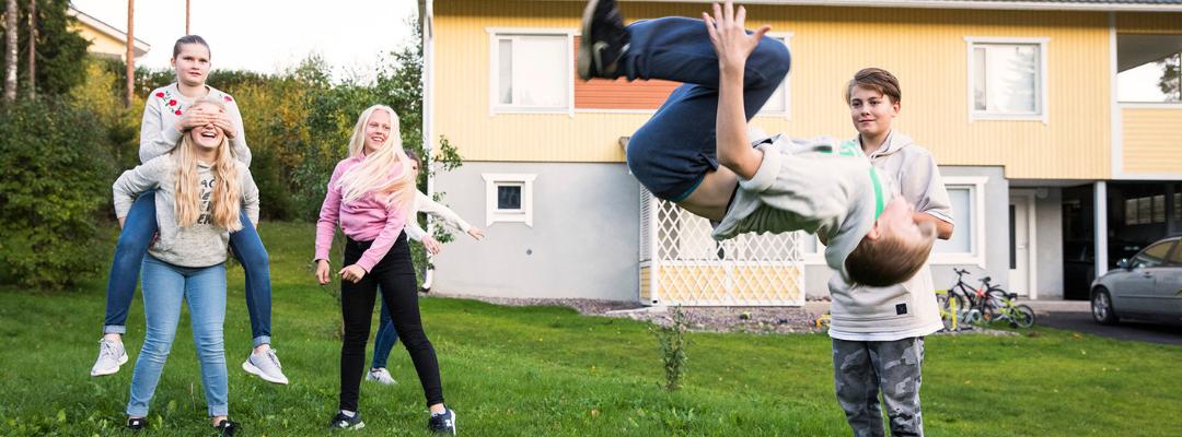 Nuorisoa nauramassa ja temppuilemassa takapihalla.