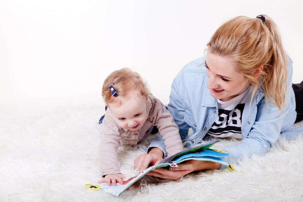 Woman showing pictures from the book to her child while lying on the floor.