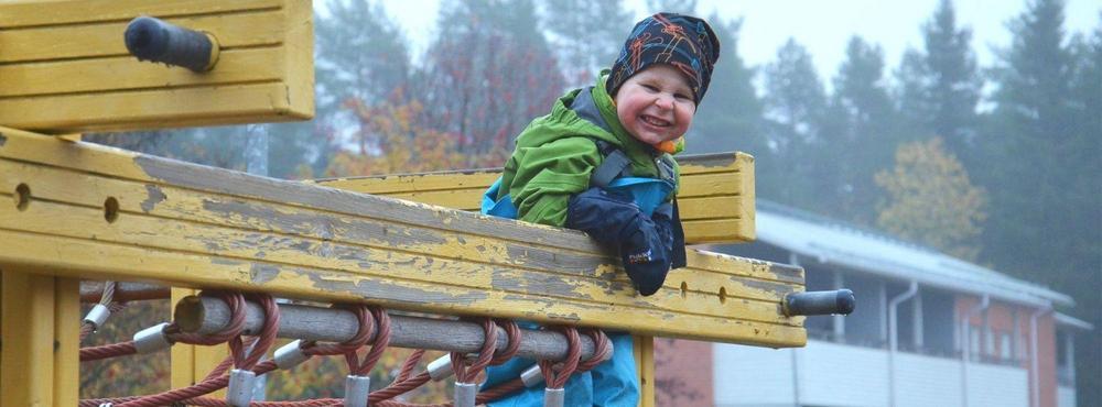 Lapsi hymyilee leikkipaikalla.