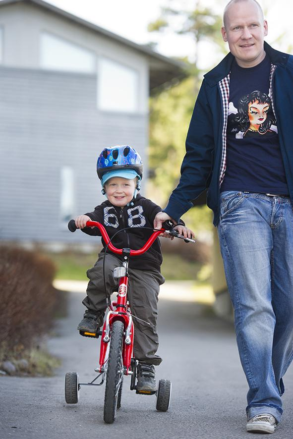 Lapsi opettelee ajamaan pyörällä vanhemman avustuksella.