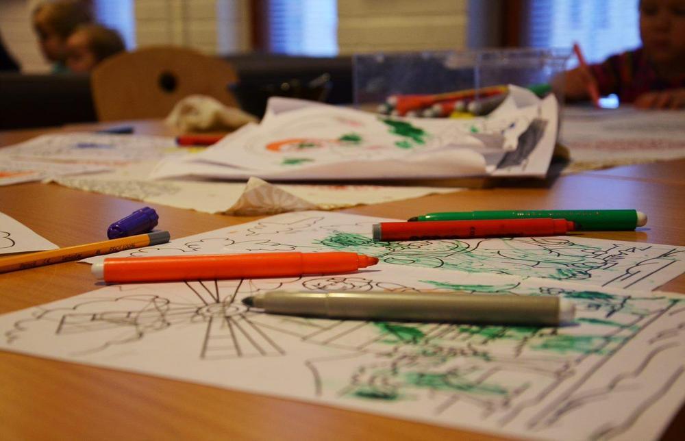 Lasten piirrustuksia ja kyniä levällään pöydällä.
