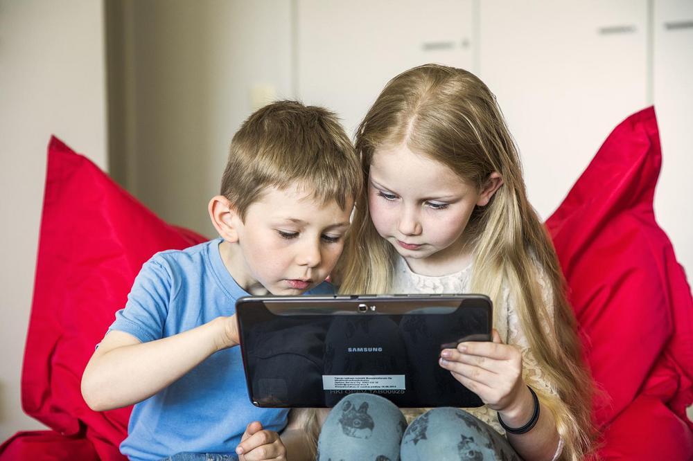 Kaksi lasta katsoo jotain yhteiseltä tabletilta.