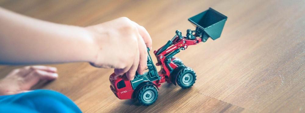 Lapsi leikkii leluautolla.