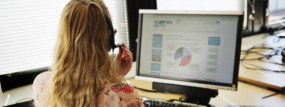 Päivystäjä puhumassa puhelua tietokoneen äärellä.
