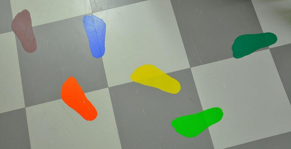 Värikkäitä jalanjälken muotoisia tarroja lattiassa.
