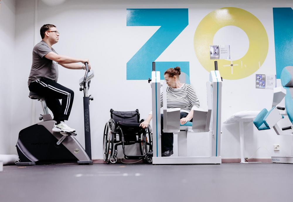 Kaksi henkilöä, joista toinen käyttää pyörätuolia, kuntosalilla.