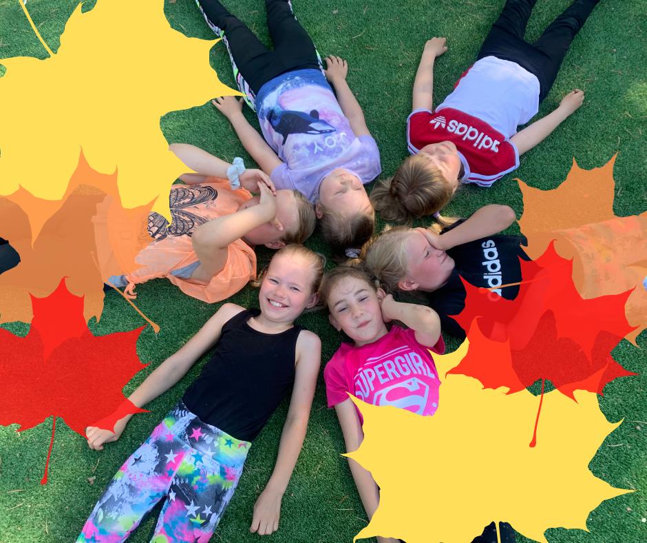 Lapsia makaamassa nurmikolla ja kuvan etuosassa syksyisiä vaahteran lehtiä.