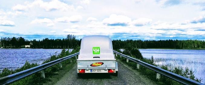 Keskellä menee tie sinisen järven yli ja keskellä tietä peräkärryn perä, jossa 4Hn logo.