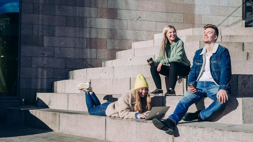 Kolme henkilöä istuu betoniportailla nauttien auringonpaisteesta.