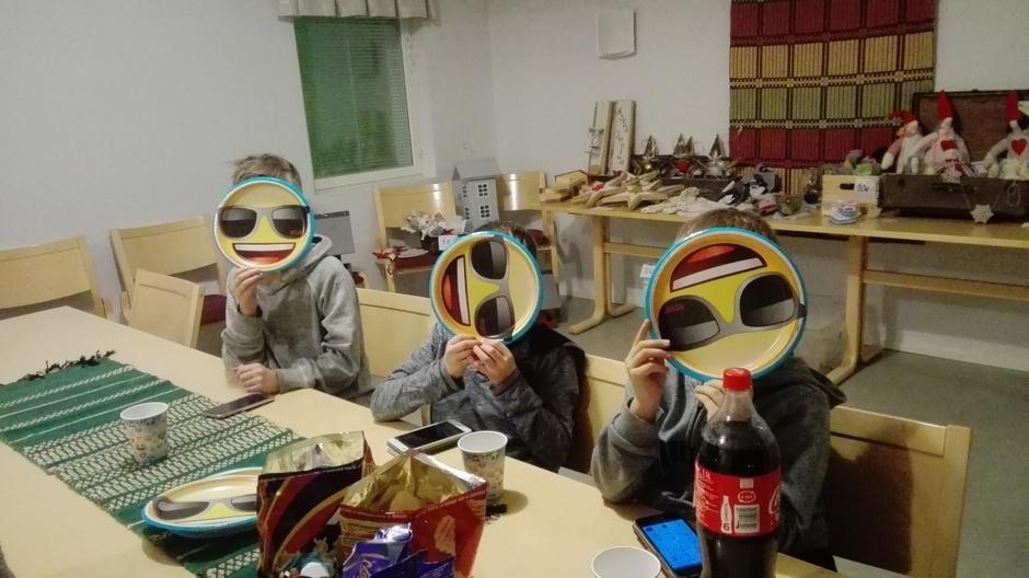 Kuvassa kolme poikaa paperilautaset kasvojen edessä. Lautasten pohjassa kuva iloisesta ilmeestä. Pöydällä herkkuja ja limsaa.