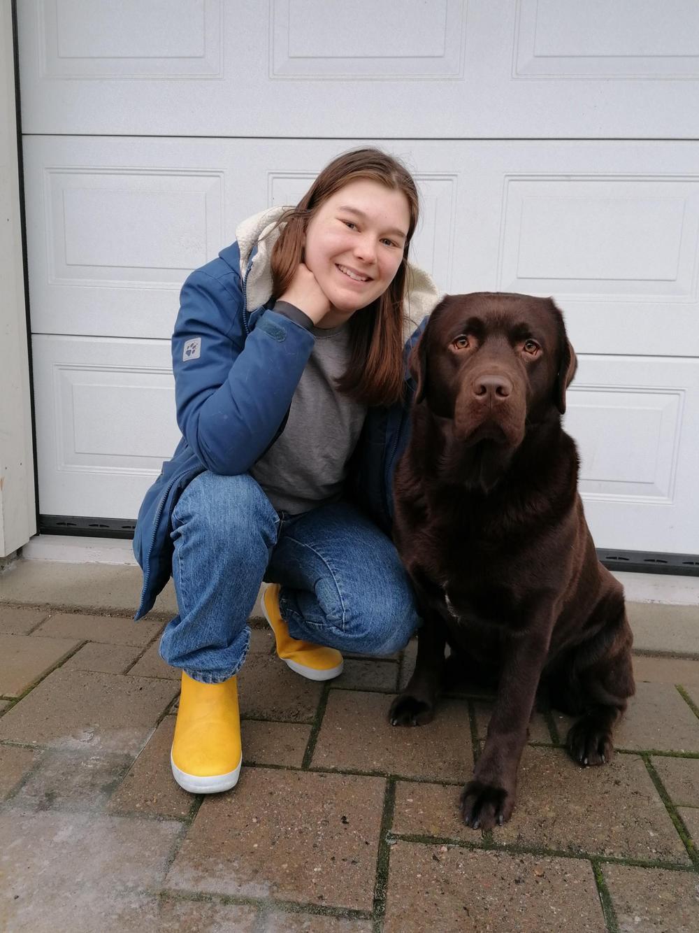Kuvassa on kyykyssä tummatukkainen tyttö ja tummanruskea koira.