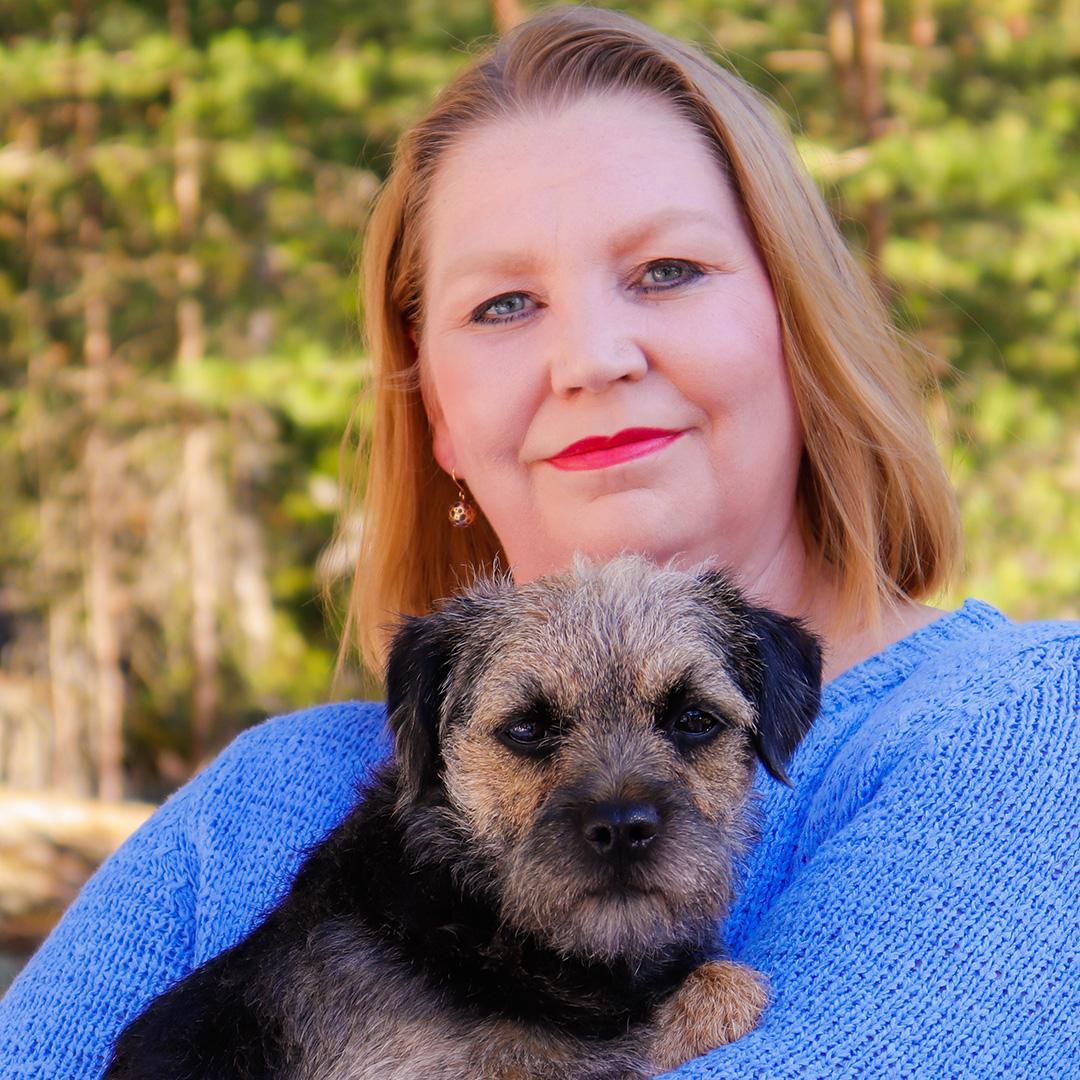 Kuvassa Maria koira sylissä