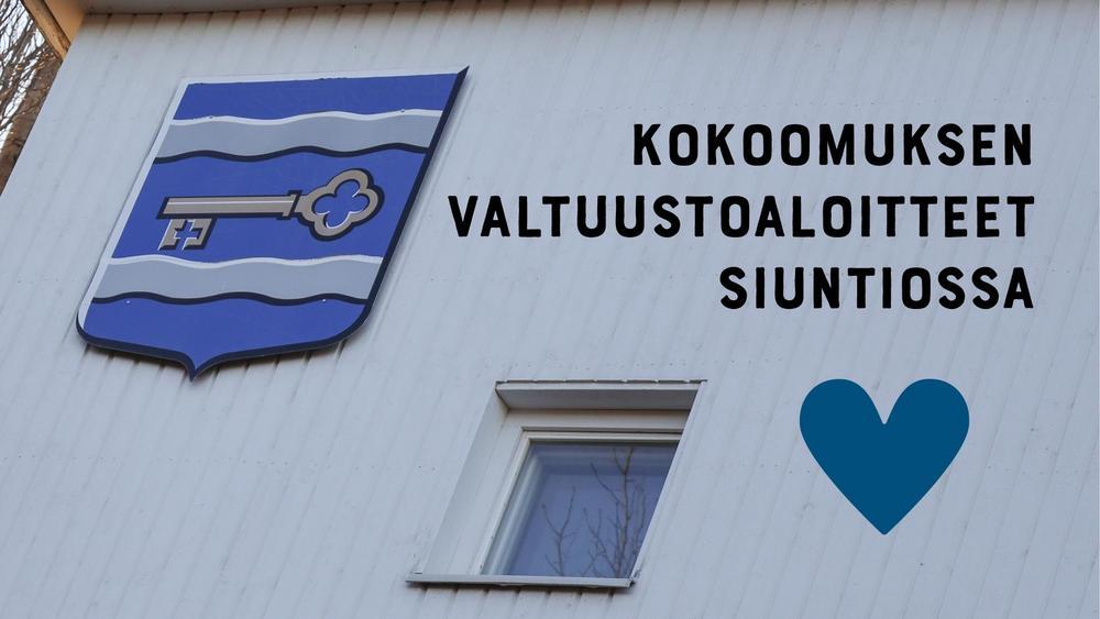 Kuvassa kunnantalon seinällä oleva vaakuna, sininen sydän ja aloitteista kertova teksti