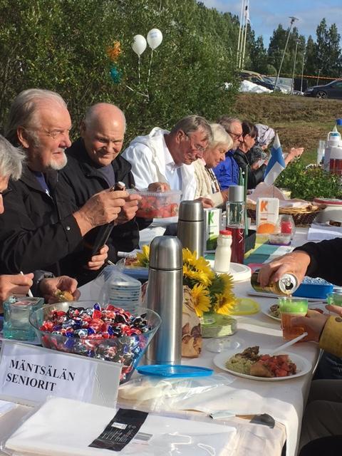 """Syödään yhdessä  """"Mäntsälän Suomi 100""""  - tilaisuudessa Urheilupuistossa. Mäntsälän seniorien pöytäseurue mukanaan paljon herkullista syötävää."""