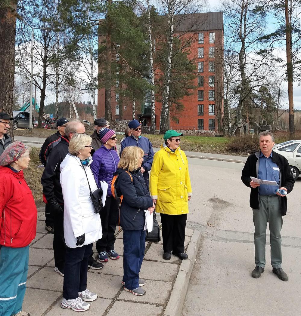 Vanhan Äänekosken keskustan kierroksen osallistujien takana uusinta uutta Äänekosken keskustaa