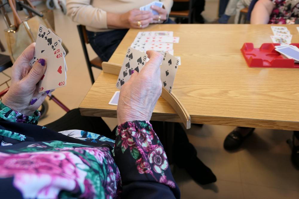 Pelikortit pelipöydällä ja pelaajien käsissä tai telineessä.