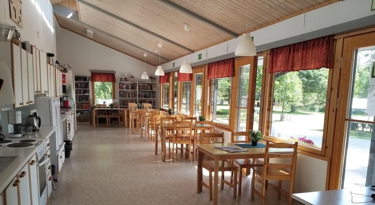 Valoisan ja avaran päärakennuksen sisätilat, näkyvissä tiskipöytiä varusteineen ja neljän hengen ruokapöytäryhmiä.