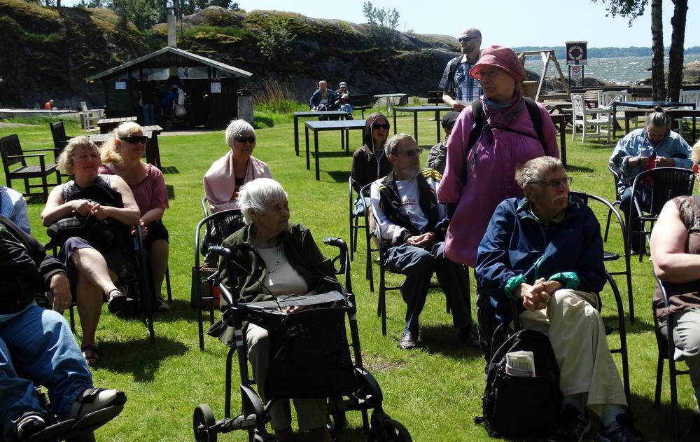 Tuoleilla istuvia ihmisiä aurinkoisella nurkikentällä. Taustalla kalliot ja meri.