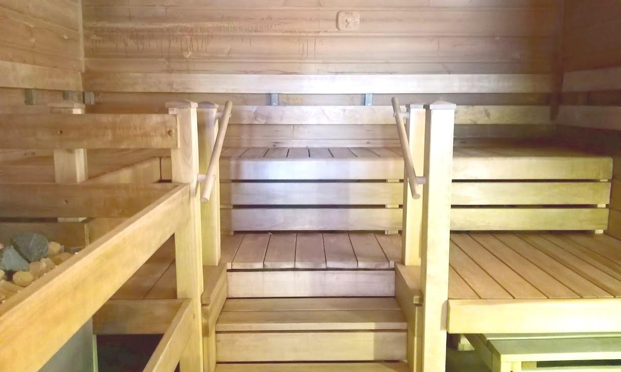 Sauna sisältä, vaaleaa puuta olevat lauteet ja kiuas.