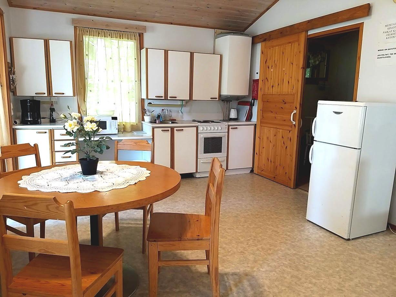 Mökki 16 sisältä, näkyvissä ruokapöytä neljälle, tiskipöytä, mikroaaltouuni, kahvikeitin, jenkkikaappi ja liukuovi wc-tilaan.