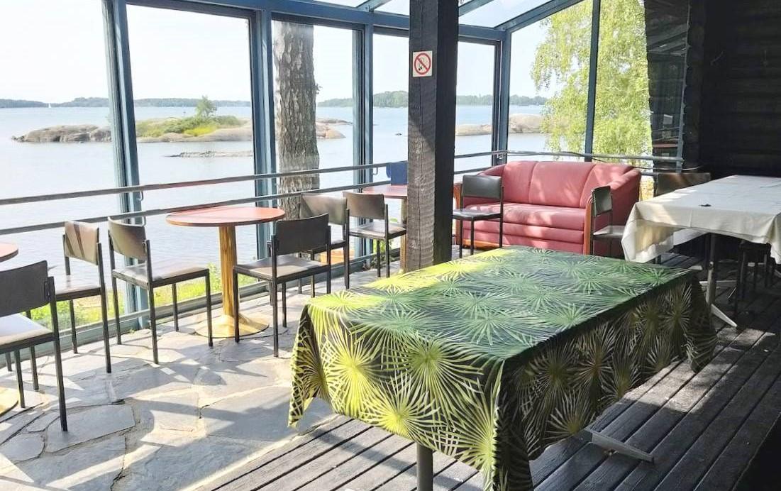 Merinäköala saunarakennuksen lasiteltulta terassilta, jossa näkyy sohva ja pöytäryhmiä.