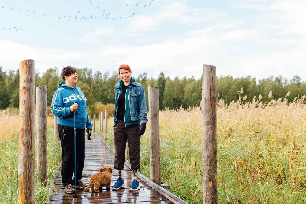 Kaksi henkilöä ja koira esteettömällä luontopolulla.