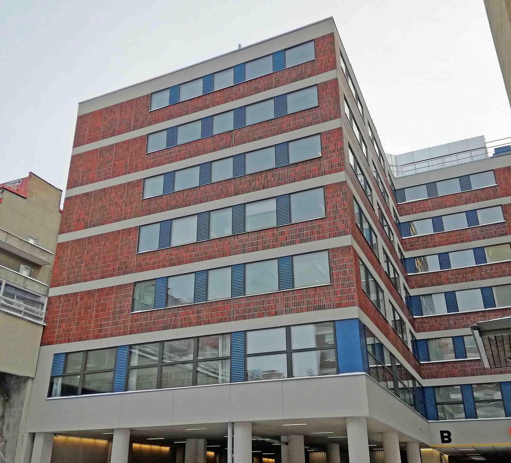 Toimihenkilöarkiston toimitilat kuvattuna ulkoa. Näkymä sisäpihan parkkipaikalta kohti B-rakennusta. Arkiston suuret ikkunat näkyvät 2. kerroksessa.