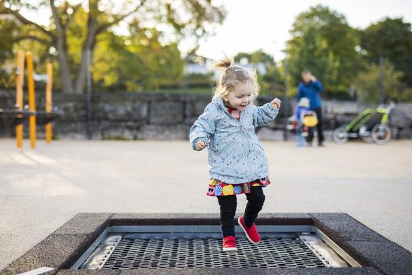 Lapsi hyppii ulkona puistossa maahan upotetulla trampoliinilla.