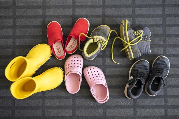 Monta paria erilaisia kenkiä lattialla.
