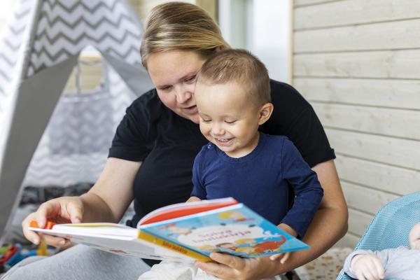 Äiti ja lapsi sylikkäin lukemassa satukirjaa.