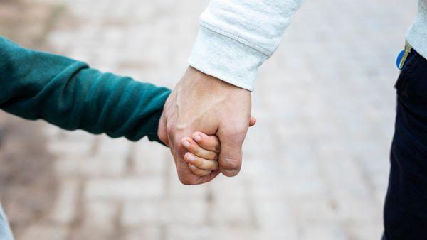 Lapsi ja aikuinen pitävät toisiaan kädestä kiinni.