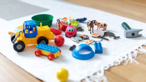 Värikkäitä leluja valkoisen maton päällä.