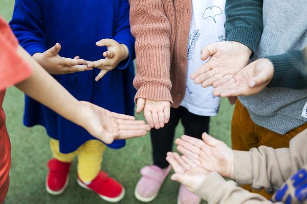 Lapsia ringissä kämmenet ylöspäin.