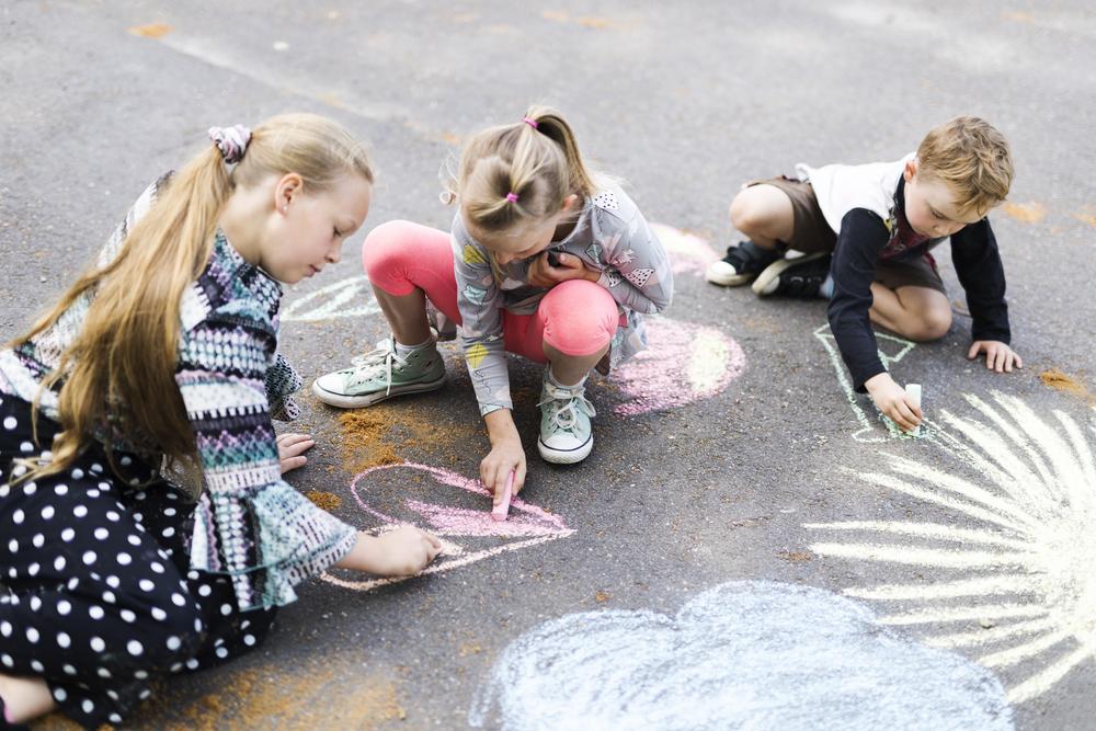 Lapset piirtävät katuliiduilla asfalttiin sydämiä, pilviä ja aurinkoja.