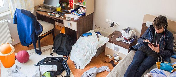 Sekainen huone, sängyllä istuu nuori pelaamassa puhelimella kuulokkeet päässä.