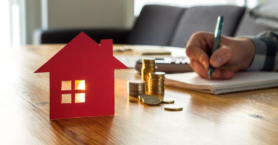 Puinen pöytä, jolla punaisesta paperista leikattu talon siluetti. Taustalla käsi, jossa kynä, jolla kirjoittaa vihkoon.