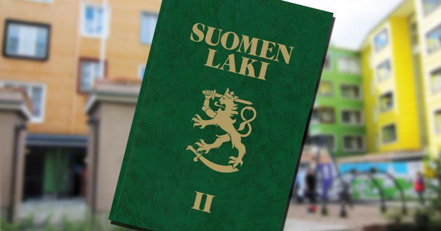 Vihreän lakikirjan kansi taustallaan kerrostaloja ja niiden piha-alue.