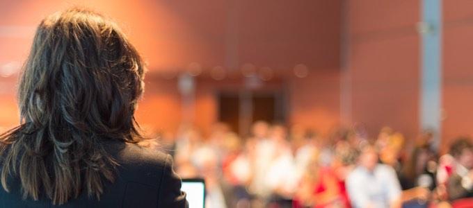 Takaapäin kuvattuna puhuja, jonka edessä yleisöä