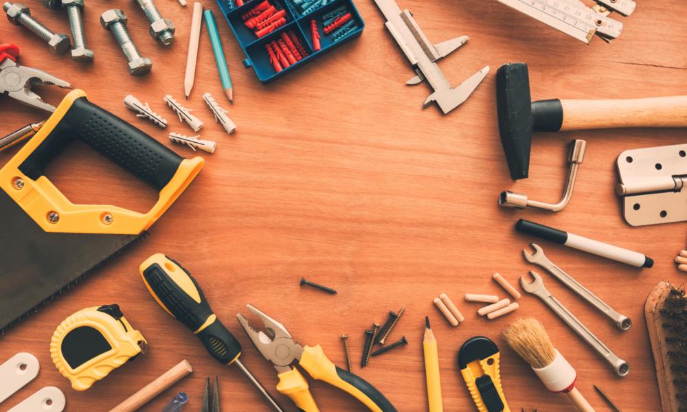 Puisella alustalla työkaluja, kuten vasara ja saha ynnä muuta.