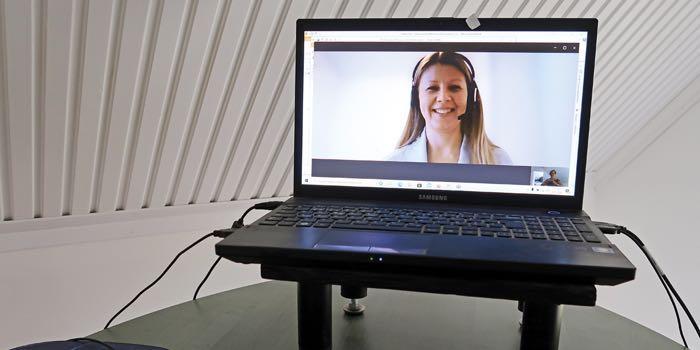 Kannettavan tietokoneen ruudulla näkyvät palaveriin osallistuvan naiset hymyilevät kasvot.