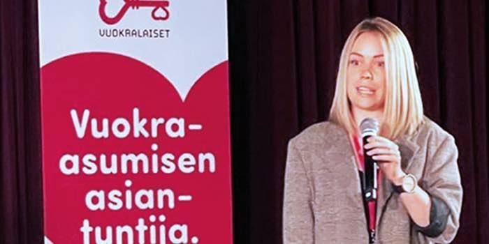 Malviina Peltonen puhumassa Vuokralaiset ry:n seminaarissa mikrofoni kädessään.
